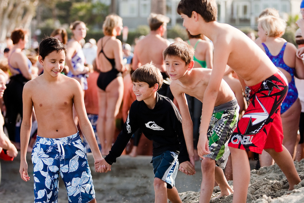 Diego Majewski, Nathan Thomson, Santiago Majewski and Zach Thomson lead the pack at the start of the Polar Plunge at La Jolla Shore Beach.