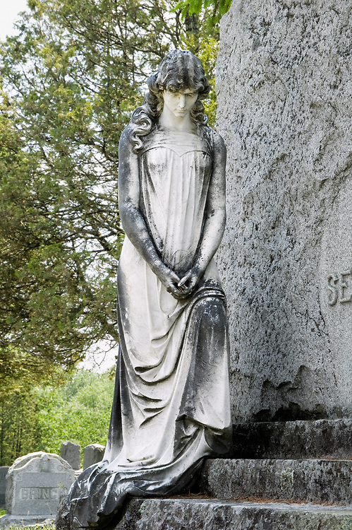 A marble cemetery statue of a sad young girl with head bowed in thought who lives on as a tarnished angel...