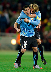 Maximiliano Pereira and Diego Forlan of Uruguay celebrate during penalty shots at the 2010 FIFA World Cup South Africa Quarter Finals football match between Uruguay and Ghana on July 02, 2010 at Soccer City Stadium in Sowetto, suburb of Johannesburg. (Photo by Vid Ponikvar / Sportida)