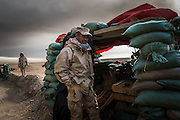 Iraqi soldiers stand guard at a military outpost in the village of Haj Ali, south of Mosul, Iraq, on December 7, 2016. As the battle to recapture the IS stronghold of Mosul progresses, Iraqi forces and paramilitary militias consolidate their gains and prepare for further advances towards the city. Toxic black smoke from the burning oil wells in the nearby town of Qayyarah fills the sky.