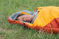 man enjoying a nap in a sleeping bag outdoors in a field