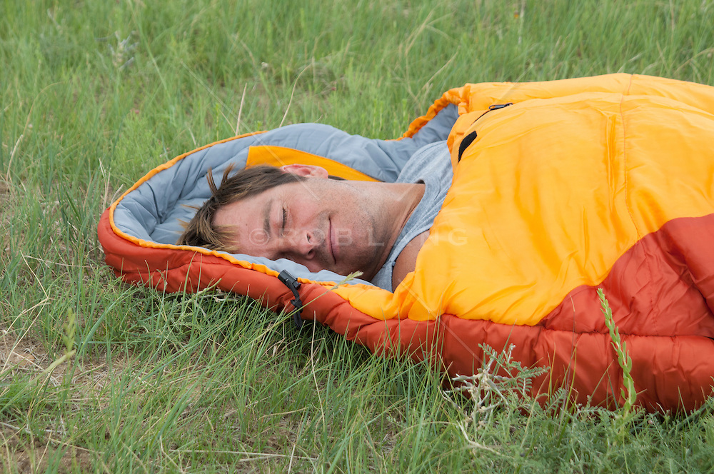 man enjoying a nap in a sleeping bag outdoors in a field