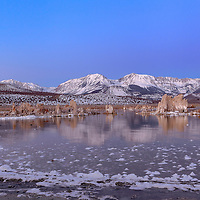 Reflections of tufas and snowy mountains the morning after a huge winter storm stirred up all this salt foam. Mono Lake, near Lee Vining, California