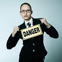 studio shot portrait of a beautiful young woman in a costume suit wearing a danger pancart sign