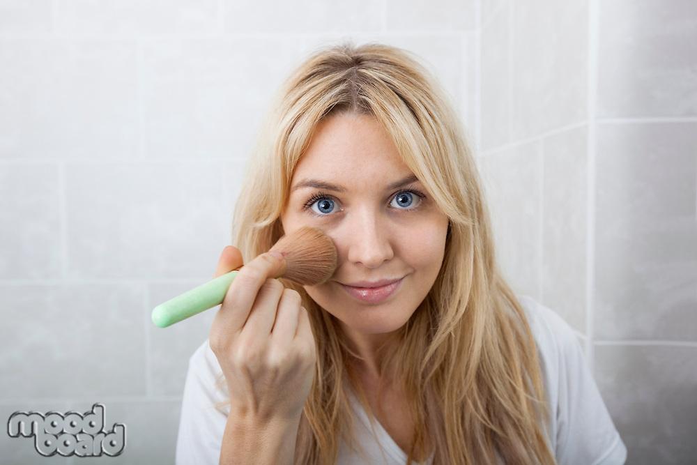 Portrait of young woman applying blush in bathroom
