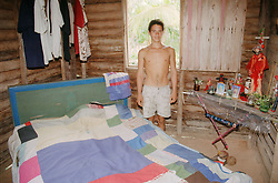 Young man standing in bedroom with patchwork bedspread and display of Santeria items in family house on farm near Banes; Cuba,