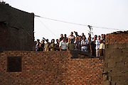 Egyptian bystanders and residents of the Manshiyet Nasr slums watch as rescue operations take place Saturday, September 6, 2008 to reach hundreds of people believed buried under the more than 70 tons of giant limestone slabs that fell on the Cairo shantytown earlier that morning. So far, authorities have recovered 64 bodies, but have struggled to get in heavy equipment that might be used to retrieve more bodies or search for survivors.