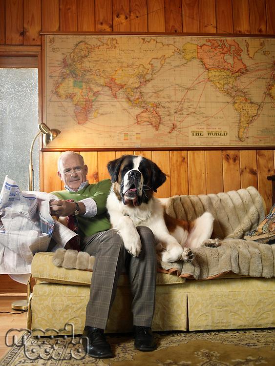 Senior man sharing sofa with large St Bernard dog