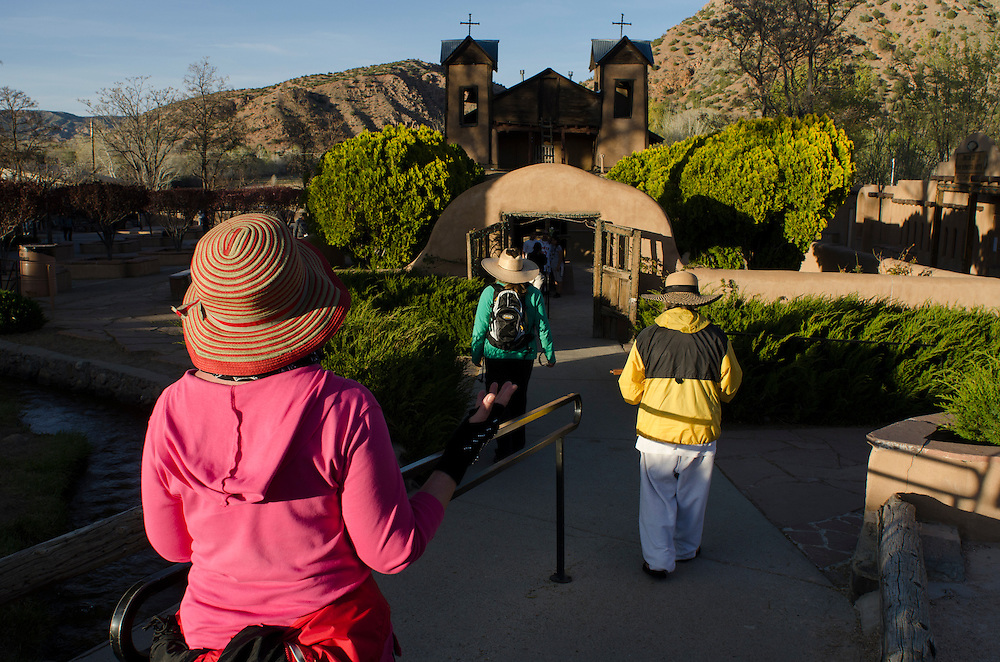 """Navajo elder Betty Box, accompanied by two friends from Colorado, enter the courtyard of El Santuario de Chimayo, Thursday, April17, 2014, having made the pilgrimage north from Santa Fe earlier that day. Pilgrims may take a small amount of Holy Dirt, believed to have healing powers, from """"el pocito"""" or """"the little well"""" inside El Santuario. (AP Photo/Jeremy Wade Shockley)"""