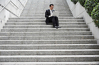 China Hong Kong business man sitting on steps using laptop low angle view