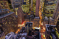The streets of Manhattan light up at night as seen from the towering rooftops.