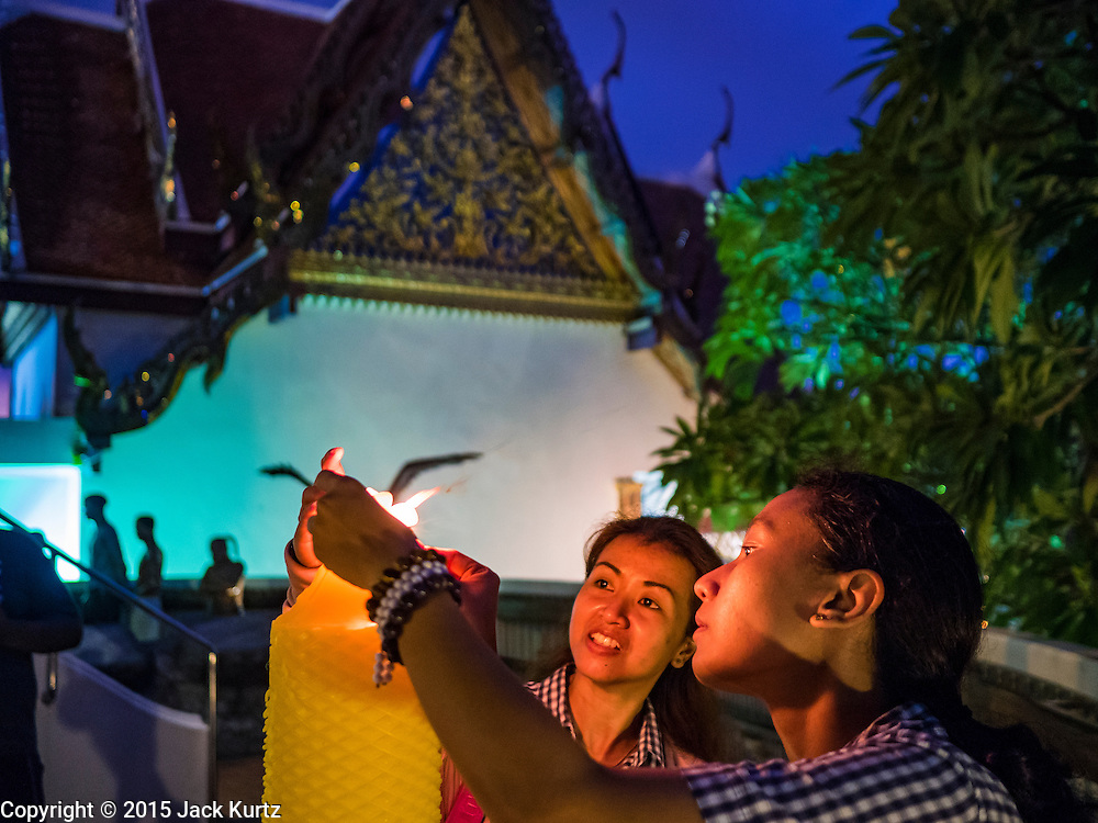 20 NOVEMBER 2015 - BANGKOK, THAILAND: Students light candles during the temple fair at Wat Saket. Wat Saket is on a man-made hill in the historic section of Bangkok. The temple has golden spire that is 260 feet high which was the highest point in Bangkok for more than 100 years. The temple construction began in the 1800s in the reign of King Rama III and was completed in the reign of King Rama IV. The annual temple fair is held on the 12th lunar month, for nine days around the November full moon. During the fair a red cloth (reminiscent of a monk's robe) is placed around the Golden Mount while the temple grounds hosts Thai traditional theatre, food stalls and traditional shows.     PHOTO BY JACK KURTZ