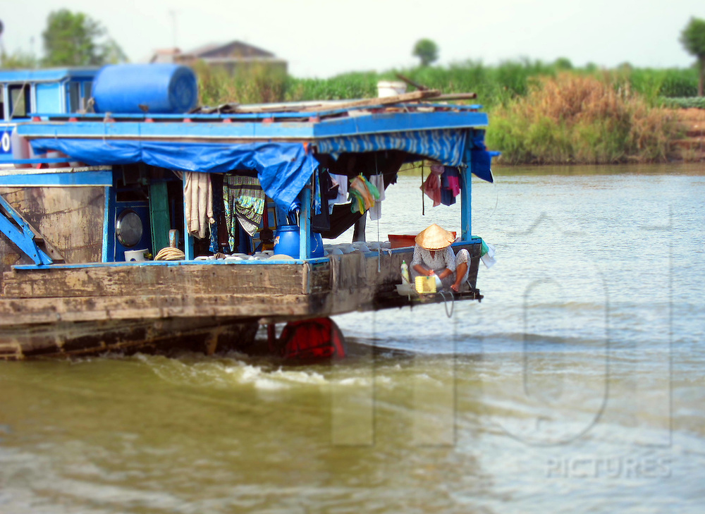 A Vietnamese woman washes dishes on the stern of her house boat, Mekong Delta, Vietnam, Southeast Asia