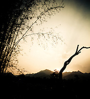 The sun sets behind a silhouette of mountains and flora, near the town of Pai, Thailand, Southeast Asia.