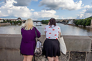 Two women are enjoying the view to river Vltava from  Charles Bridge in Prague. The Charles Bridge (Czech: Karlův most) is a famous historic bridge that crosses the Vltava river in Prague, Czech Republic and is probably the Nr.1 tourists magnet in the city.