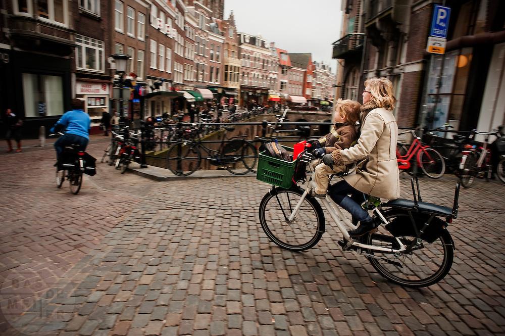 Met een kind voorop fietst een vrouw door Utrecht