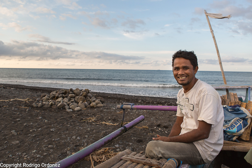 """H. Parhan, 35, poses for a photograph by the beach in Lepek Loang, Belanting, Sambelia district, East Lombok, West Nusa Tenggara province, Indonesia. He is a fisherman and a member of the local committee. The village's community action plan identified water erosion as a risk in this area and acknowledged it had washed away part of the local cemetery. Now a wall is being built to protect it. """"In the graveyard are our relatives. I am really happy about the wall."""""""
