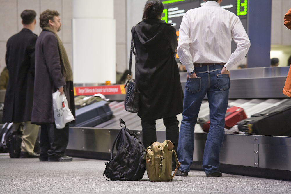 Air travellers waiting for their luggage to arrive on the airport's carousel.