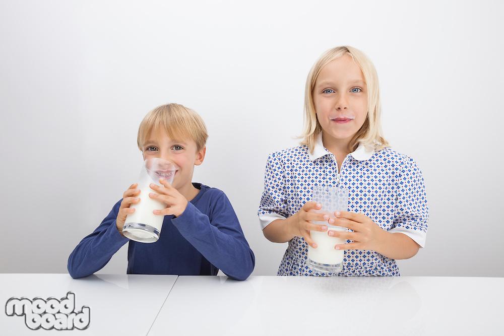 Portrait of children drinking milk at table