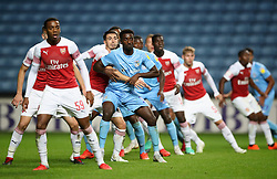 Coventry City's Jordy Hiwula grapples with Arsenal's Julio Pleguezuelo