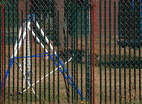 a chainlink fence with vertical plastic slats overlays a pattern of diamonds and vertical lines of green and red with diagonal lines of blue and white of a broken swingset on a grassy enclosure in Tacoma, Washington, USA