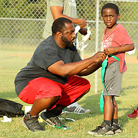 """Theodus Brewer, of Tupelo, helps his son, Trenton, 5, with his flag football belt so they can get into the game on Thursday night at the """"Father Son Fun Day"""" at Theron Nichols Park in Tupelo."""