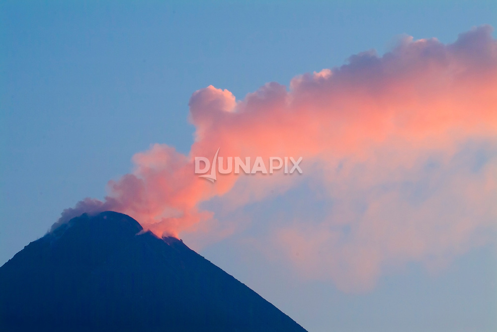 "A solftara hundreds of meters high billows from the summit of Mount Merapi, by dawn's first light on 10 May 2006. Steam and sulfurous gases rise from a lava dome growing 50,000 cubic meters per day and now measuring some 1.3 million cubic meters. Scientists and seers alike feel confident an eruption is imminent--the question remains when. The longer the dome builds, the more likely it will dislodge a flank of the peak and unleash a violent explosion. Home to 20,000 people, and one of the most active volcanoes in the ""ring of fire"", Merapi is rated as one of 15 of the world's most hazardous volcanoes, according to the International Association of Volcanology and Chemistry of the Earth."
