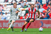 Charlie Wyke (#9) of Sunderland AFC holds off Andy Cannon (#14) of Portsmouth FC during the EFL Sky Bet League 1 match between Sunderland and Portsmouth at the Stadium Of Light, Sunderland, England on 17 August 2019.