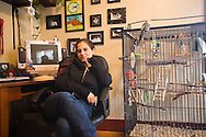 "Margaret B. Jones in her office in her home in Eugene, Oregon.  Her bird, ""Chuck"" is sitting on the cage next to her."