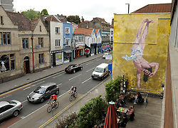 © Licensed to London News Pictures. 11/06/2013. Bristol, UK.  A mural titled Jesus Breakdancing by artist Cosmo Sarson on the wall by The Canteen bar on Stokes Croft in Bristol.  Cosmo won a competition sponsored by The Canteen to paint the mural, which was made with 1kg of gold glitter.  The mural was inspired by a breakdancing performance at the Vatican for Pope John Paul II.  11 June 2013.<br /> Photo credit : Simon Chapman/LNP