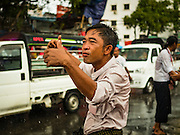 09 NOVEMBER 2015 - YANGON, MYANMAR: A man stands in the rain at NLD headquarters Monday. Thousands of National League for Democracy (NLD) supporters gathered at NLD headquarters on Shwegondaing Road in central Yangon to celebrate their apparent landslide victory in Myanmar's national elections that took place Sunday. The announcement of official results was delayed repeatedly Monday, but early reports are that the NLD did very well against the incumbent USDP.     PHOTO BY JACK KURTZ