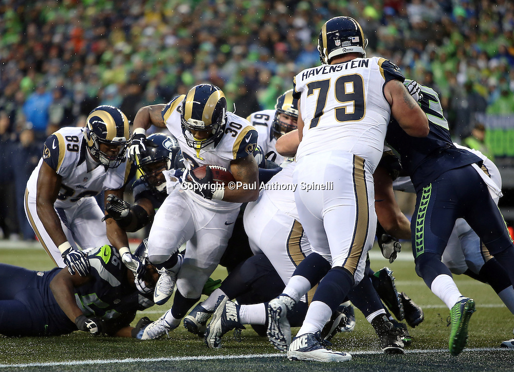 St. Louis Rams running back Todd Gurley (30) gets a block at the goal line from St. Louis Rams offensive tackle Rob Havenstein (79) as he runs for a 2 yard touchdown that gives the Rams a 23-10 fourth quarter lead during the 2015 NFL week 16 regular season football game against the Seattle Seahawks on Sunday, Dec. 27, 2015 in Seattle. The Rams won the game 23-17. (©Paul Anthony Spinelli)