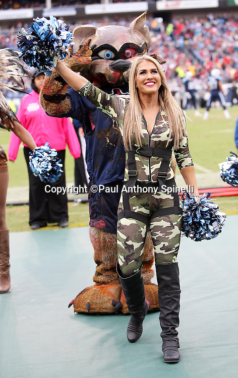 The Tennessee Titans mascot, T-Rac, salutes from behind as a Tennessee Titans cheerleader dressed in a Halloween military costume waves her pom poms as she cheers for the Tennessee Titans during the 2015 week 7 regular season NFL football game against the Atlanta Falcons on Sunday, Oct. 25, 2015 in Nashville, Tenn. The Falcons won the game 10-7. (©Paul Anthony Spinelli)