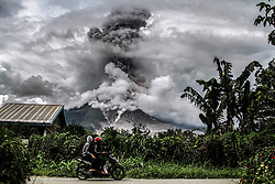 January 3, 2018 - Karo, North Sumatra, Indonesia - Indonesian people ride past a road as Mount Sinabung spews thick smoke in Karo, North Sumatra. Mount Sinabung roared back to life in 2010 for the first time in 400 years, after another period of inactivity it erupted once more in 2013, and has remained highly active since. (Credit Image: © Ivan Damanik via ZUMA Wire)