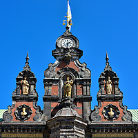 Detail of Statues on Rådhuset in Malmö, Sweden <br /> The upper façade of the Rådhuset in Malmö deserves inspection. It is the design of Helgo Zettervall.  In 1860, this architect was given liberties to decide how the original town hall should have looked when it was built in the mid-16th century. Notice the statues flanking the clock tower. On the lower right is Mathias Flensburg. He was a shipping magnate who expanded Malmö's port during the 19th century. On the lower left is Jörgen Knock. He minted coins, was a significant landowner and was the town's mayor during the early 16th century.
