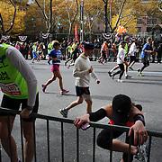 Athletes stretching as runners make their way along First Avenue in Manhattan, New York, during the ING New York Marathon. New York, USA. 3rd November 2013. Photo Tim Clayton