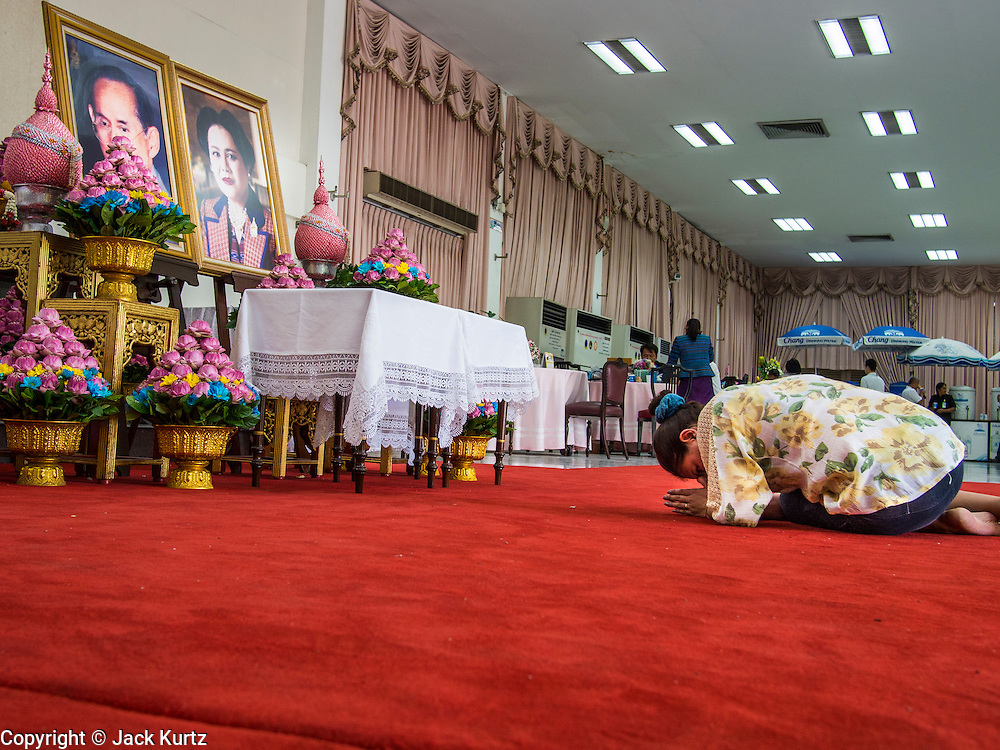 01 AUGUST 2013 - BANGKOK, THAILAND: A woman prostrates herself in front of photos of Bhumibol Adulyadej, the King of Thailand, and his wife, Queen Sirikit, who have both been living in Siriraj Hospital. The King, 85, was discharged from the hospital, Thursday where he has lived since September 2009. He traveled to his residence in the seaside town of Hua Hin, about two hours drive south of Bangkok, with his wife, 80-year-old Queen Sirikit, who has also been treated in the hospital for a year.      PHOTO BY JACK KURTZ