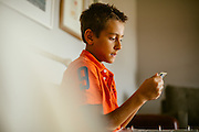 Boy looks through photo album. Country lifestyle documentary portraits. <br /> Photographed by editorial lifestyle photographer Nathan Lindstrom<br /> <br /> Nathan Lindstrom Photography<br /> <br /> © 2015 Nathan Lindstrom