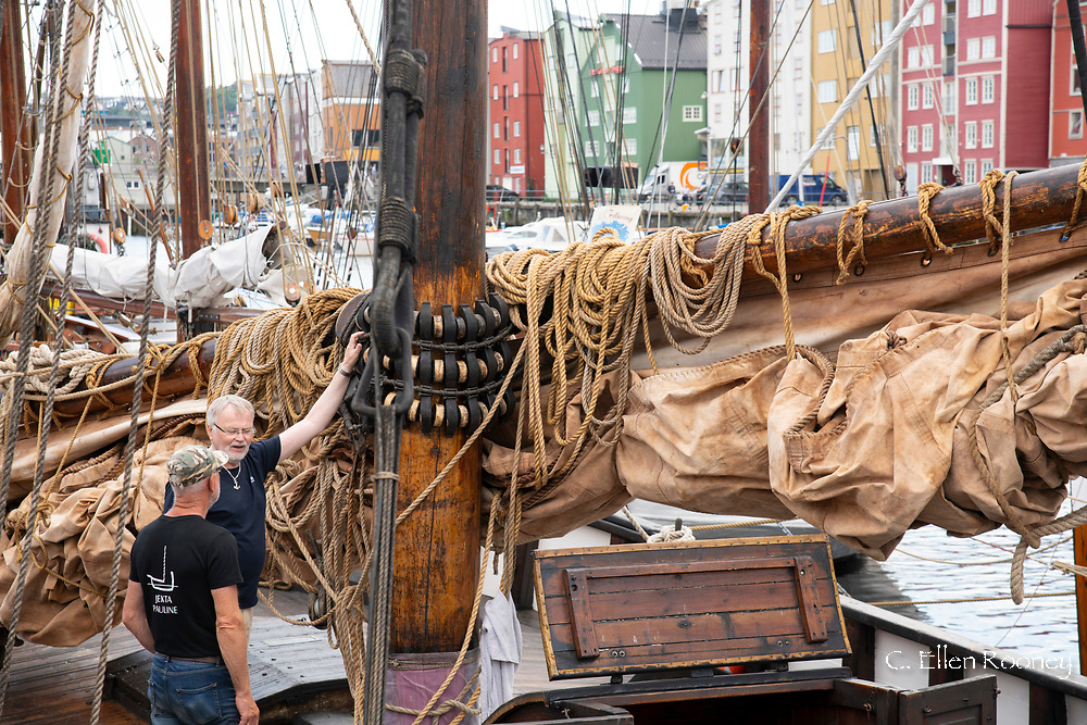 crew members next to a masted schooner at the old boat festival in Tronheim, Trondelag, Norway