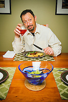Portrait of man drinking wine and eating dinner.