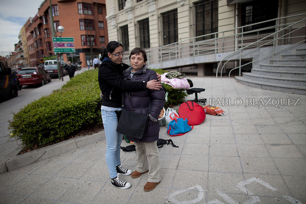 A friend hugs Amalia Torres 51, (R) next to her belongings one day before her eviction takes place outside the Madrid's Council Housing Office where she spent the night claiming to stop her eviction on April 3, 2013 in Madrid, Spain. The Mortgage Holders Platform (PAH) and other anti evictions organizations are organizing 'escraches' since several weeks ago outside Popular Party deputies houses and offices to demand the vote for a Popular Legistative Initiative (ILP) to stop evictions, regulate dation in payment and social rent.