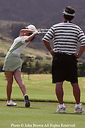 Fifteen year old Michelle Wie practices her swing on the driving range as her father BJ looks on prior to the 2005 SBS LPGA Women's Open at Turtle Bay Resort in Kahuku, Hawaii.