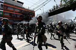 Thai army soldiers advance past a burning bus as they face off anti - government protesters during pitched battles on the streets of Bangkok, Thailand, 13 April 2009. Thai Prime Minister Abhisit Vejjajiva declared a state of emergency in Bangkok to quell anti-government protests that forced the cancellation of the ASEAN summit in Pattaya. Thai soldiers fired shots at protestors driving buses at them and used tear gas against demonstrators blocking a main road junction in Bangkok in a major escalation of political violence in the kingdom