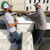 Adam Robison | BUY AT PHOTOS.DJOURNAL.COM<br /> Justin White and Nathan Jackson, employees for Tupelo Public Works Department, change bulbs out on the roof line above Rogers Realty and Appraisal Company on Broadway Street on Monday in Tupelo.