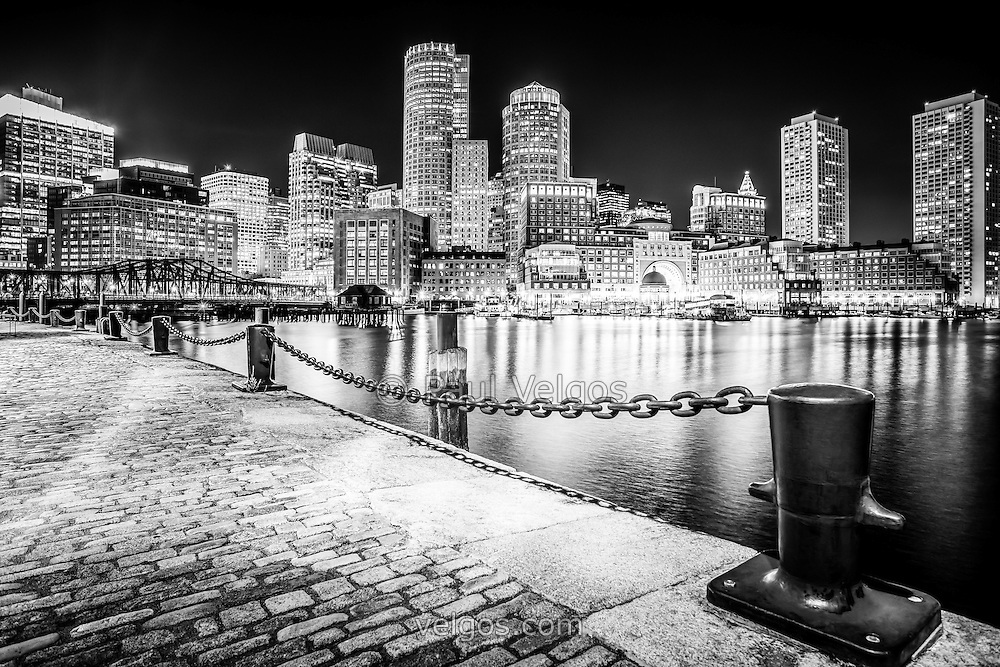 Boston skyline at night black and white picture. Includes the Boston Harborwalk waterfront, downtown Boston skyscrapers and Nothern Avenue Bridge.