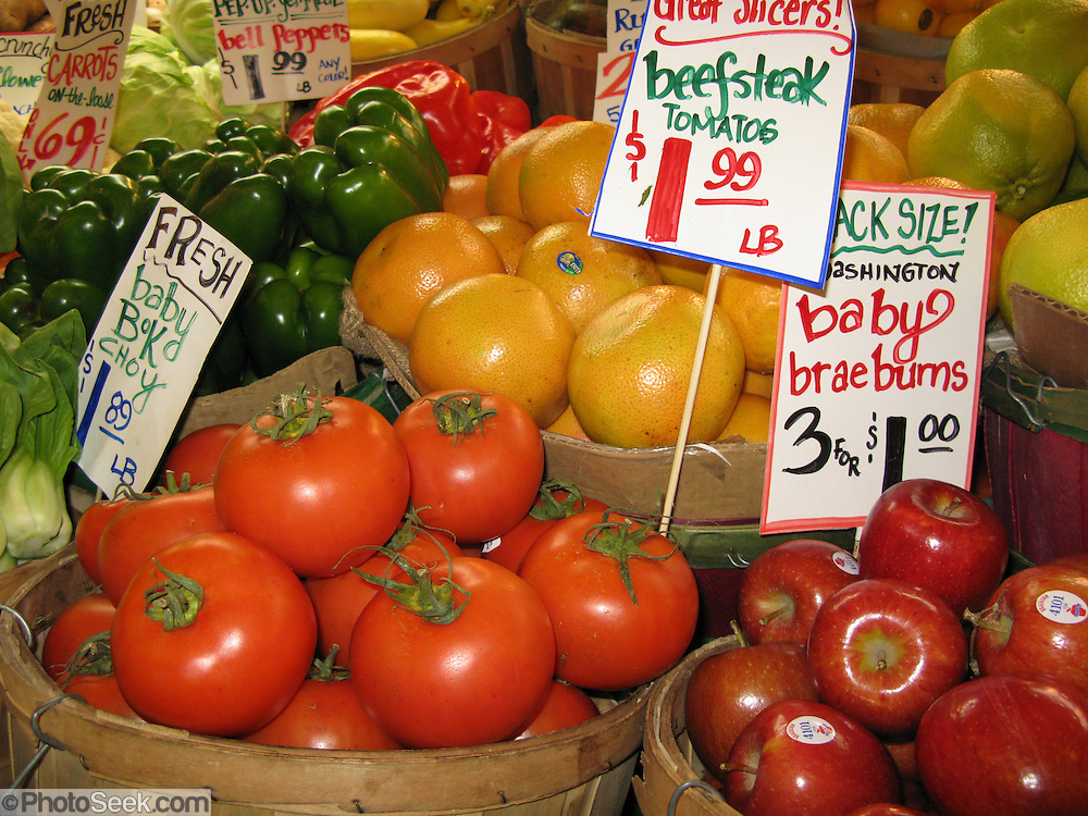 Vegetables, braeburn apples, tomatoes, grapefruit for sale at Pike Street Public Market Center and Farmers Market, in downtown Seattle, Washington, USA.