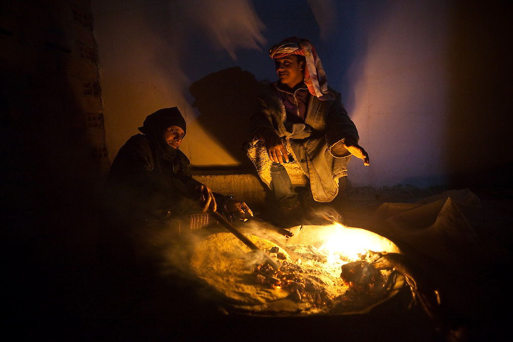 A bedouin woman cooks flat bread in a fire outside her family's home in Umm Sayhoun, the bedouin village just outside Petra, Jordan.