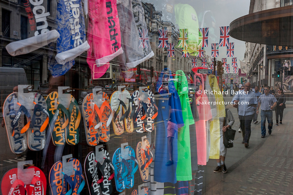 Window display for international brand Superdry, with the reflections of British national flags in London's Regent Street.