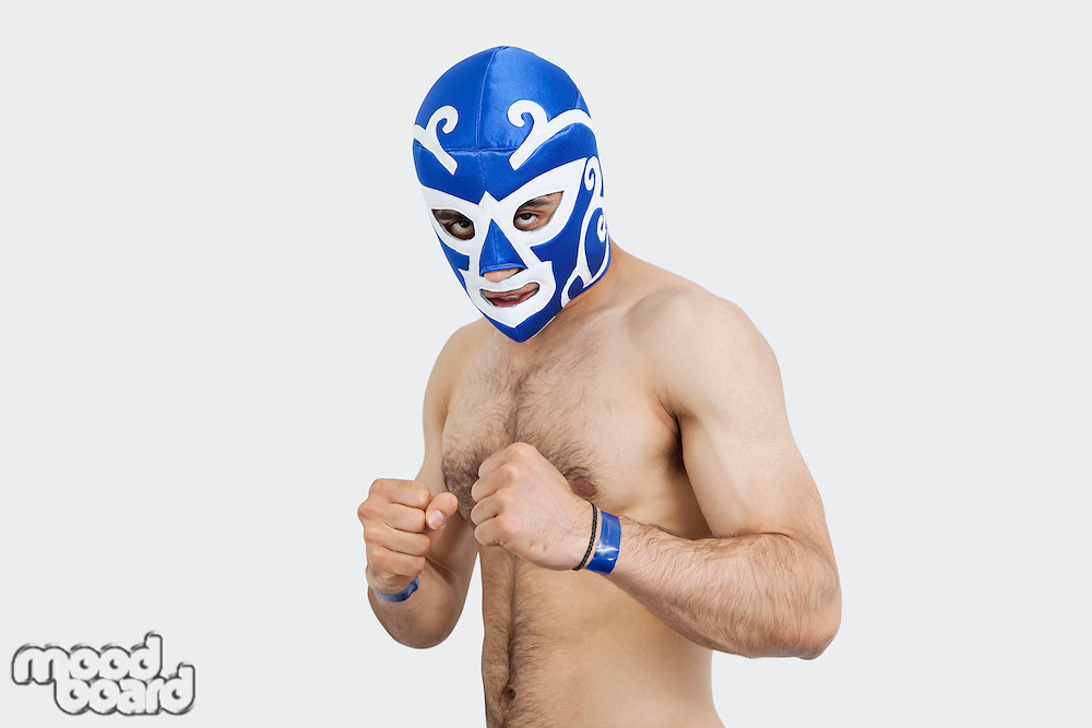 Portrait of a young shirtless male wrestler wearing wrestling mask over gray background