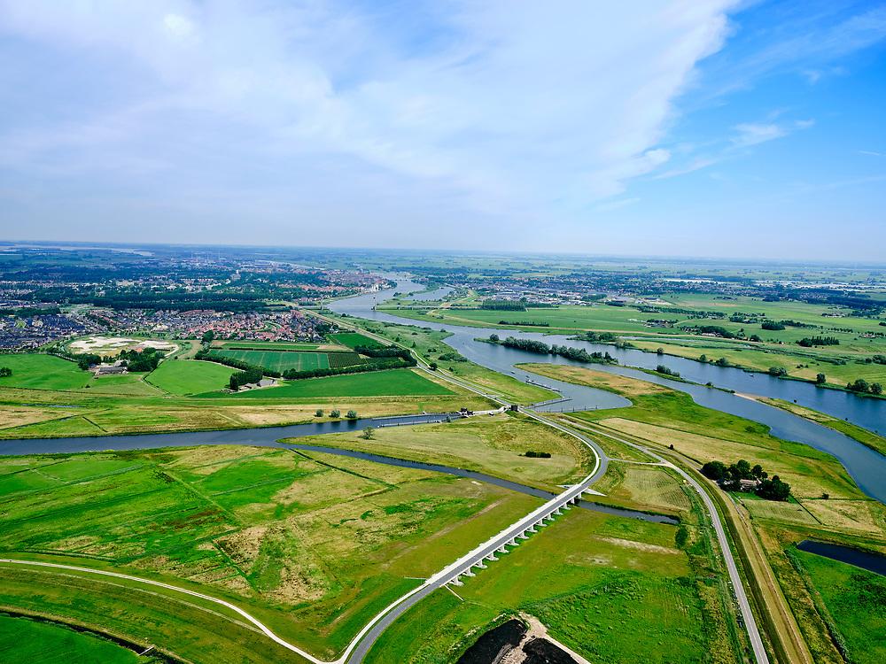 """Nederland, Overijssel, Gemeente Kampen; 21–06-2020; zicht op de IJssel en de Onderdijkse Waard, Kampen in de achtergrond, In de voorgrond het inlaatwerk van het nieuw aangelegde Reevediep, Het Lange End.<br /> Het Reevediep is aangelegd in het kader van het project Ruimte voor de Rivier om bij hoogwater water af te voeren voordat dit het nabij gelegen Kampen bereikt, direct naar het IJsselmeer, de 'bypass Kampen'. Het Reevediepgebied is ook een natuurgebied en vormt een ecologische verbindingszone tussen rivier de IJssel en Drontermeer.<br /> View of river IJssel with the Onderdijkse Waard, Kampen city in the background. The newly constructed inlet of the Reevediep, The Long End.<br /> The Reevediep has been constructed as part of the Room for the River project, and functions to discharge high waters before reaching the nearby Kampen, directly to the IJsselmeer, the """"bypass Kampen"""". The Reevediep area is also a nature reserve and forms an ecological connecting zone between the river IJssel and Drontermeer.<br /> <br /> luchtfoto (toeslag op standard tarieven);<br /> aerial photo (additional fee required)<br /> copyright © 2020 foto/photo Siebe Swart"""